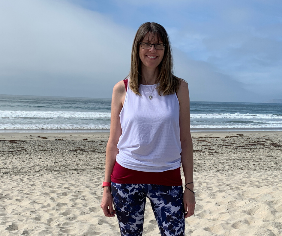 zoe standing in a white tshirt and colourful trousers on a beach