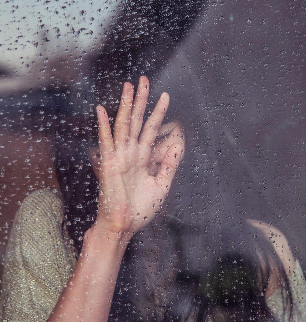 woman behind a rain splashed glass