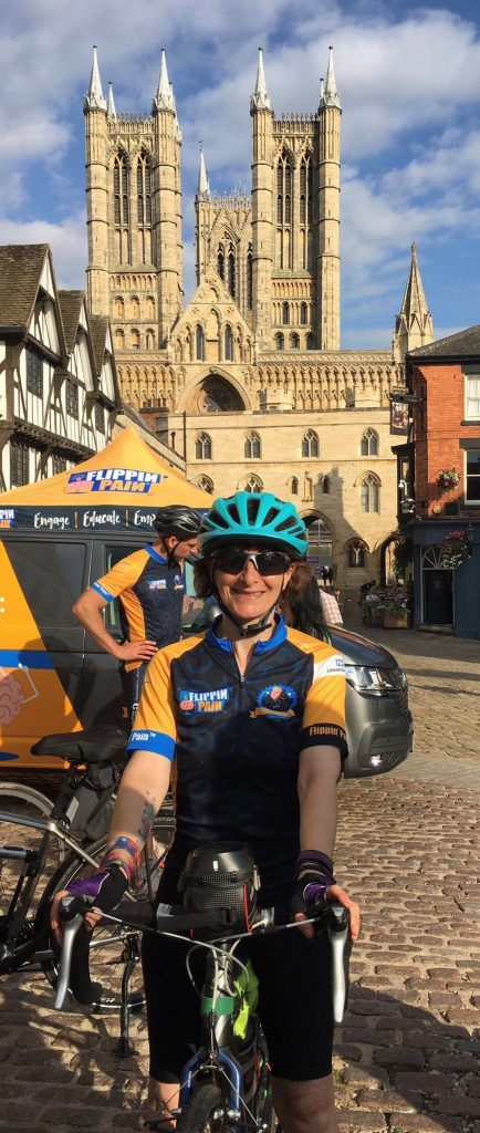 Niki in front of Lincoln Cathedral in Flippin Pain branded cycling gear and her bike smiling very happily